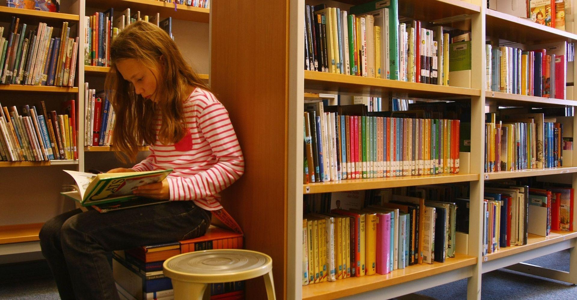 Una ragazzina legge un libro seduta su uno sgabello in una libreria
